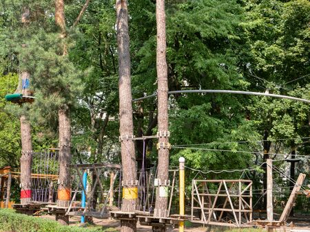 rope climbing amusement adventure park on trees in forest .