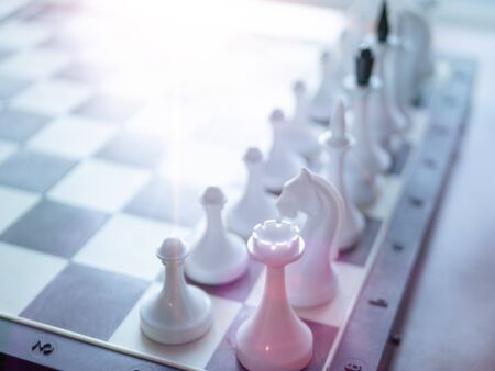 chess board with only white figures. selective focus on nearest figure and light leak coming from top