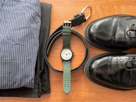 top view on businessman clothing set - pants, shirt, pair of black shoes, wrist watch and leather belt Imagens