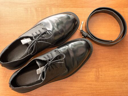 pair of elegant glossy black formal man shoes and leather belt on wooden table