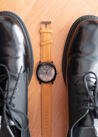 classic mechanical wrist watch lay between pair of man black formal shoes. top view Imagens