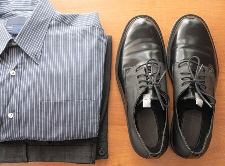 everyday set of mans wear clothes for white collar worker - pants, formal shirt and pair of glossy shoes
