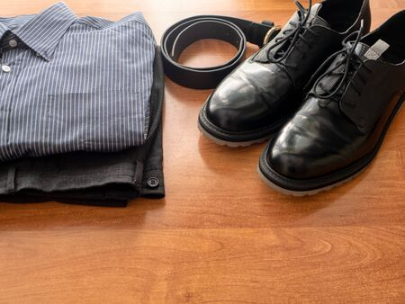 daily wardrobe man clothes set for office worker. pair of black glossy dress shoes, leather belt, pants and formal shirt on wooden desk