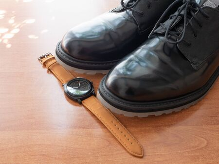 pair of man black glossy formal shoes and wrist watches on wooden desk