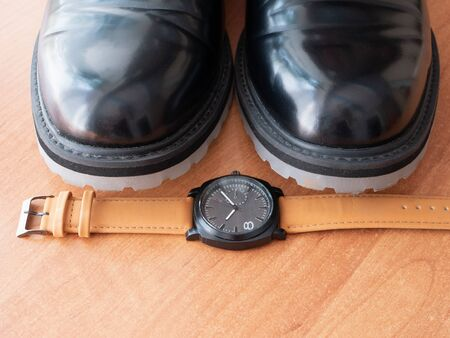 closeup of mans wrist watch by pair of stylish elegant black classic shoes