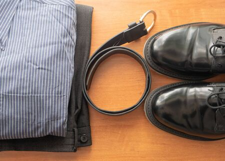 set of man businessman wear clothes on a desk - pair of black shoes, pants, shirt and leather belt