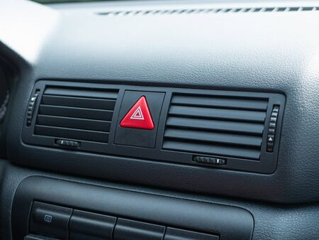 closeup of triangle red accident Stop Emergency Light Button on Car dashboard plate