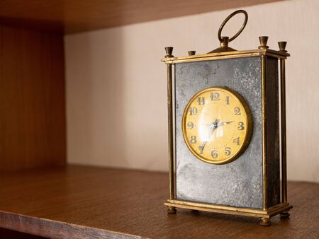 close-up of old vintage table black marble mechanic clock on wooden shelf with golden dial face and metallic circle for moving