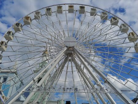 huge Ferris wheel at city center. entertainment for adults and children. blue sky with clouds on background. low angle image