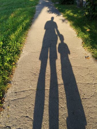 two long shadows of father and son on asphalt sidewalk walking together at summer sunny day Archivio Fotografico