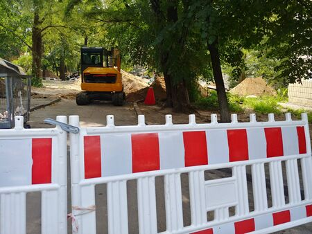 fence at construction site with piles of ground and excavator on background