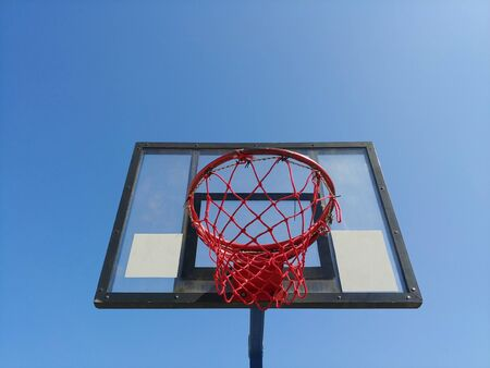 front image of basketball basket ring from the bottom with clear blue sky on background