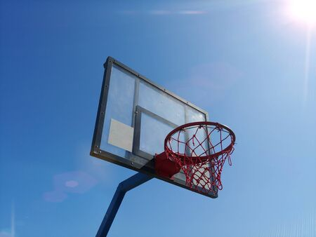 side view of basketball ring basket outdoor with clear blue sky on background and bright sun at corner with flares and sunbeams