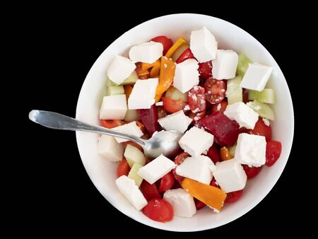 white bowl of greek salad isolated cutout on black bakground. red tomatoes, feta cheese, cucumbers, bulgarian pepper. Imagens
