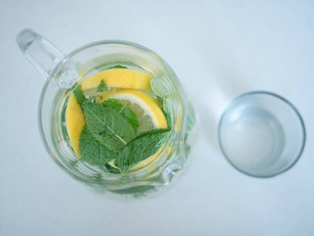 top view on jug of homemade lemonade with mint leaves and lemon slices or lime wedges and glass cup.