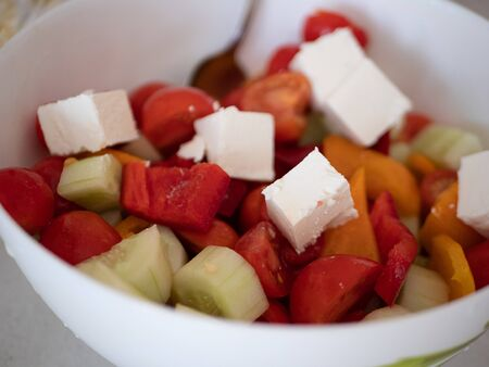 close-up of ceramic bowl with homemade fresh greek salad made of tomatoes, bulgarian pepper, green cucumbers and feta cheese. vegan diet meal.