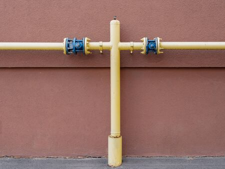 yellow water gas utility pipe branching with painted concrete wall on background t-connection. image with lot of copy space.