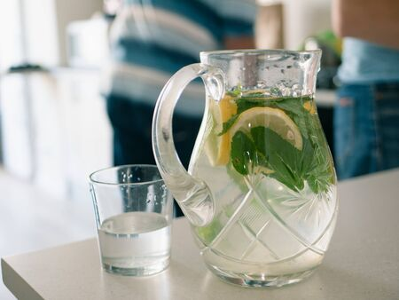 homemade lemonade with lemon wedges slices and mint leaves on a wooden table. blurred people on background.