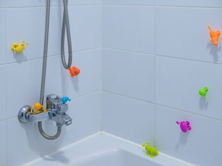 empty kid's bathroom with white tiles and lot of sticky colorful toys on walls