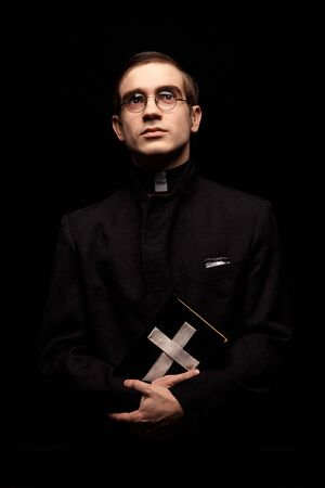 Portrait of handsome young catholic priest with prayer book against black background looking up