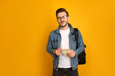 Young journalist wearing glasses, a white t-shirt and denim jacket over yellow background, holding his black bag over the shoulder,a pen and notebook, looking at the camera mysteriously. Stock fotó