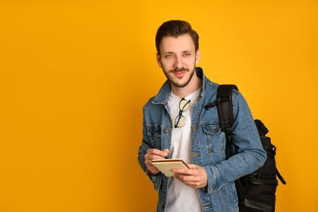 Young journalist with glasses over his collar,in a white t-shirt and denim jacket over yellow background, holding his black bag over the shoulder,a pen and notebook, looking sideways mysteriously