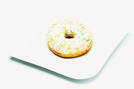 A donut on a plate and a white background.
