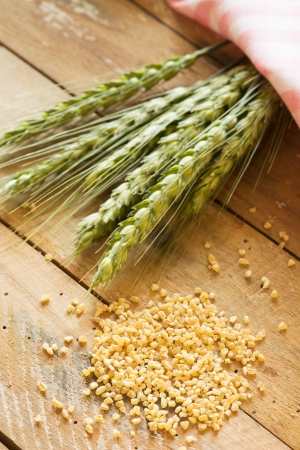 Green wheat and wheat grains on wooden table photo