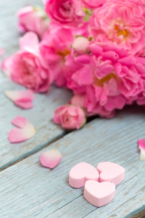 Gentle pink rose and heart on wooden table  photo