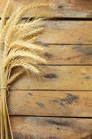Sheaf of Wheat over Wooden table.Harvest concept. photo