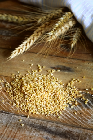 Wheat and wheat grains on wooden table. Shallow depth of field. photo