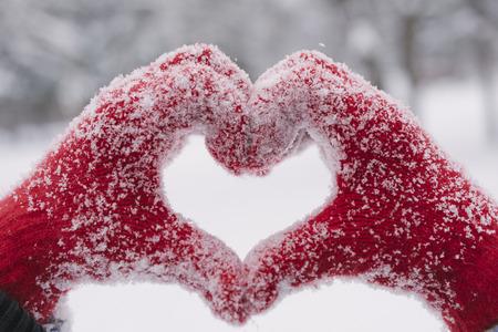 雪に覆われた手でハートマークを作る女性
