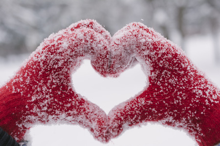 mitten: Woman making heart symbol with snowy hands