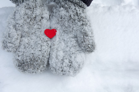 Snowy mittens with tiny red heart. Valentines concept.