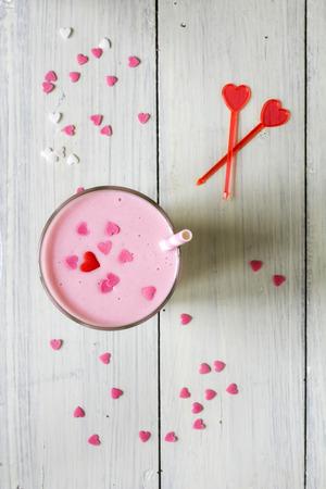 Pink milkshake sprinkled with sugar hearts photo