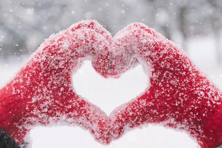 corazon humano: Mujer que hace s�mbolo del coraz�n con las manos cubiertas de nieve