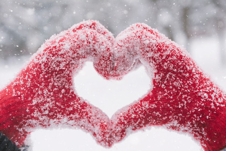 love tree: Woman making heart symbol with snowy hands