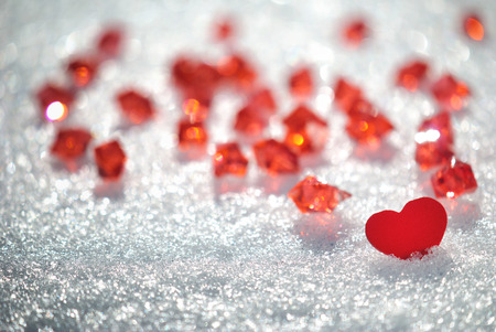 Red heart in glittering snow with red crystals Stock Photo