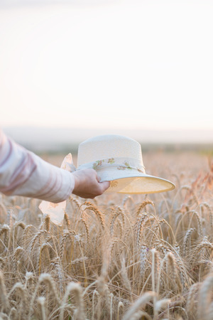 Woman holding a straw hat over ripe wheat