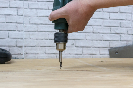 Screwing the screw into the board during the repair