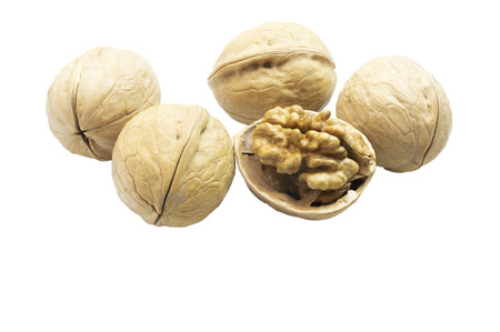 Chopped walnut and whole walnuts on white background