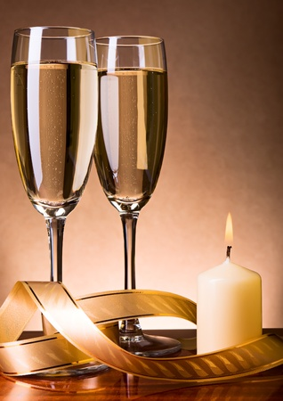 Two glass with champagne and celebratory ribbon with burning candle
