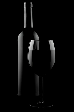 Bottle and glass of red wine on black background