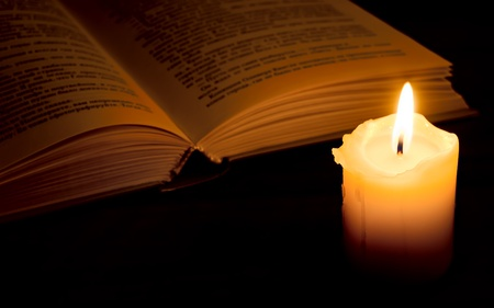 Open book and burning candle on dark