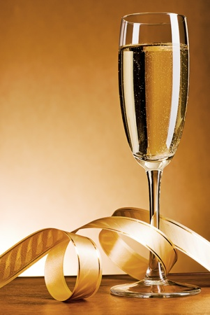 Glass with champagne and celebratory ribbon Stock Photo
