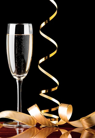 Holiday glass of champagne and decorative ribbons on black background