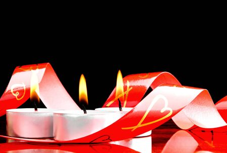 Red ribbon and the burning candles Stock Photo - 8876231