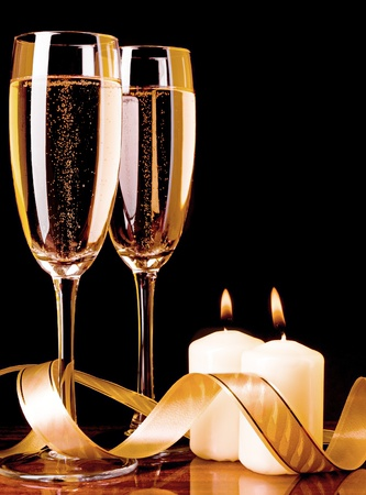 Two glass with champagne and celebratory ribbon with two burning candles photo