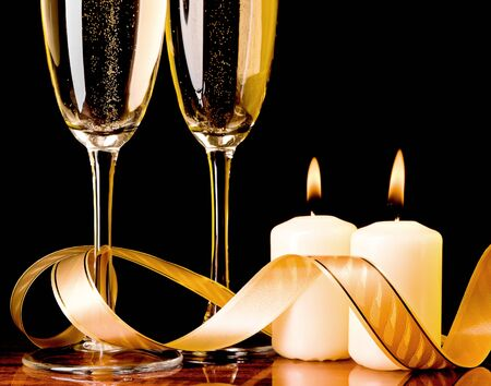 Two glass with champagne and celebratory ribbon with two burning candles Stock Photo