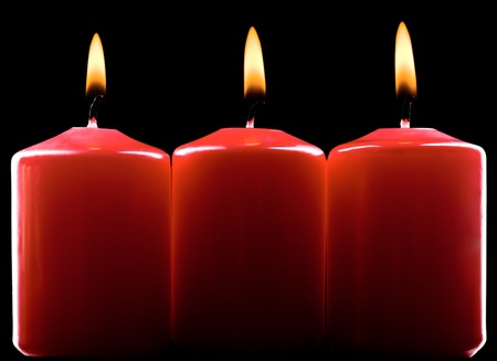 Three red burning candles over black photo